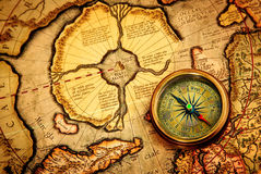Vintage compass lies on an ancient map of the North Pole. Royalty Free Stock Photos