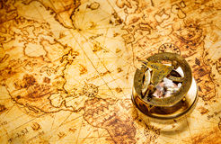 Vintage compass lies on an ancient world map. Royalty Free Stock Photos