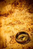 Vintage compass lies on an ancient world map. Royalty Free Stock Photography