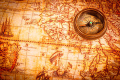 Vintage compass lies on an ancient world map. Royalty Free Stock Image