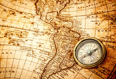 Vintage compass lies on an ancient world map. Stock Photos
