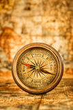 Vintage compass lies on an ancient world map. Stock Photography