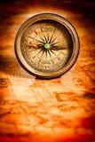 Vintage compass lies on an ancient world map. Stock Photos