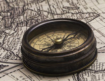 Vintage compass on the map. The old brown metal compass on a world map background stock image