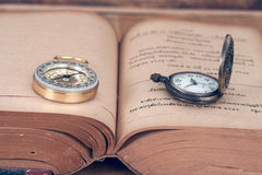 Vintage Compass and pocket watch on books. royalty free stock photography