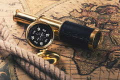 Vintage compass and spyglass on old world map Royalty Free Stock Photos
