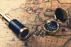 Vintage compass and spyglass on old world map Stock Images
