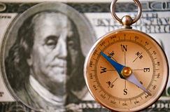 Vintage Compass Standing In Front of 100 USD Bill. Conceptual Vintage Compass Instrument Standing In Front of a 100 US Dollar Bill, Emphasizing the Portrait of Stock Photos