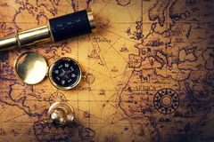 Vintage compass and telescope on old world map Stock Photography