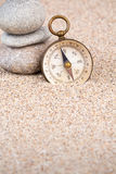 Vintage compass with three pebble stones portrait view Royalty Free Stock Photos