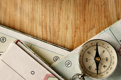 Vintage Compass on Wooden Table with Folded Maps Stock Images