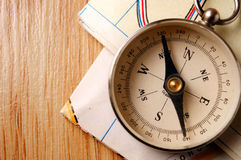 Vintage Compass on Wooden Table with Folded Maps Stock Image