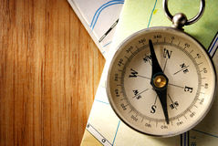 Vintage Compass on Wooden Table with Folded Maps Royalty Free Stock Image