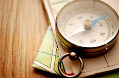 Vintage Compass on Wooden Table with Folded Maps Royalty Free Stock Photo