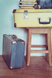Vintage Composition with old books, suitcases and stool. Stock Photos