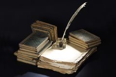 Vintage concept. Old fountain pen, books and inkwell on a black Stock Image