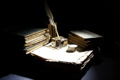 Vintage concept. Old fountain pen, papers and inkwell and silver coins on a black Stock Photography