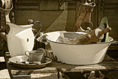 Vintage Cooking Utensils and Items. Vintage cooking utensils, pans, dishes, basin and pitcher in sunlight next to an authentic old west style chuck wagon at an Stock Images