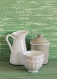 Vintage cookware - enameled jar, pitcher and white ceramic bowl on a green wooden surface Stock Photography
