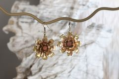 Vintage cooper-brass earrings in the form of a flower on the white stone stock image