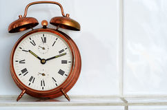 Vintage copper alarm clock on the mantelshelf. Old-fashioned copper alarm clock on the mantelshelf royalty free stock image