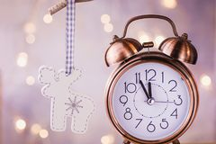 Vintage Copper Alarm Clock Showing Five Minutes to Midnight. New Year Countdown. Wood Christmas Tree Deer Ornament Hanging. On Branch. Glittering Garland Lights royalty free stock photo