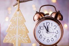 Vintage Copper Alarm Clock Showing Five Minutes to Midnight. New Year Countdown. Wood Christmas Tree Ornament Hanging on Branch. Glittering Garland Lights royalty free stock images
