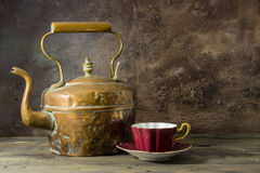 Vintage copper kettle and bone-china teacup. Old copper kettle with contrast of magenta bone china cup, on a wooden table royalty free stock images