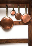 Vintage copper pans hung on wooden shelf Stock Images