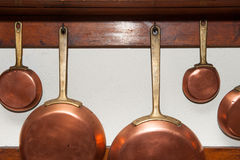 Vintage copper pans hung on wooden shelf Royalty Free Stock Photos