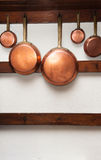Vintage copper pans hung on wooden shelf Royalty Free Stock Photo