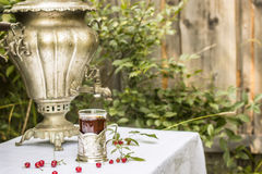 Vintage copper samovar in a cup holder and a glass of hot tea st. Ands on the table covered with a white tablecloth are scattered beside cherry and raspberry in Stock Images
