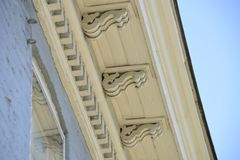 Vintage corbels and dentil molding on old building. With vivid blue sky stock photography