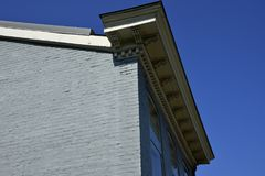 Vintage corbels and dentil molding on old building. With vivid blue sky stock image
