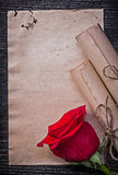 Vintage corded paper rolls red rose on wooden Royalty Free Stock Photos