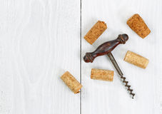 Vintage corkscrew with old corks on white wooden boards Royalty Free Stock Images