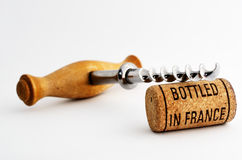 Vintage corkscrew and wine cork with inscription bottled in Fran. Vintage old corkscrew and wine cork with inscription bottled in France royalty free stock image