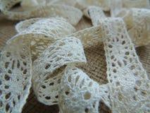 Vintage cotton cream lace on burlap background. Stock Image