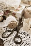 Vintage lace trims and sewing items. Vintage cotton lace trims on wooden spools and sewing items lying on the table stock photos
