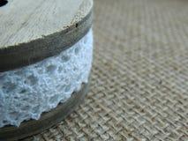 Vintage cotton white lace on wooden bobbin on burlap background. Royalty Free Stock Photos