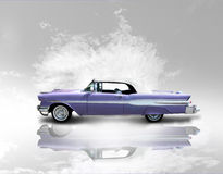 Vintage coupe. A two door lavender convertible vintage American automobile with white walled tires and reflection on a slighty cloudy surface.  This is a Stock Photography