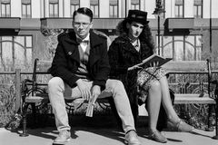 Vintage couple looking serious reading book on the bench royalty free stock photos