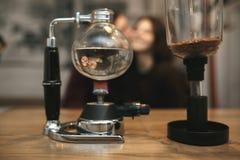 Vintage couple preparing coffee with vacuum coffee maker.Coffee Royalty Free Stock Image