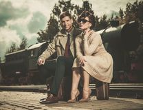 Vintage couple sitting on suitcases. Beautiful vintage style couple sitting on suitcases on  train station platform Stock Photos