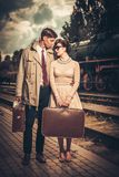 Vintage couple on train station platform. Vintage style couple with suitcases on train station platform Stock Photo