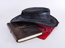 Vintage Cowboy Gear. Vintage leather cowboy hat, leather covered diary, and a red handkerchief on a white background Stock Photo