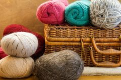Vintage Crafts Wicker Chest Box Clews Balls of Colorful Wool Yarn Red Blue White Beige Grey Knitting Hobby. Header Banner for Websites Close up Royalty Free Stock Photo