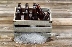 Vintage crate with ice cold bottle beer on rustic wooden boards. Vintage crate filled with bottled beer and crushed ice on rustic wooden boards Stock Photography