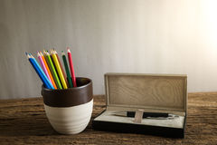 Vintage crayons in thegray cup with pen box on the wood floor Stock Image