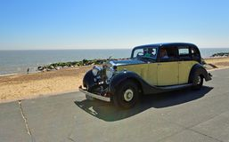 Vintage Cream and Black Rolls Royce Motor Car being driven along Seafront Promenade. Stock Images